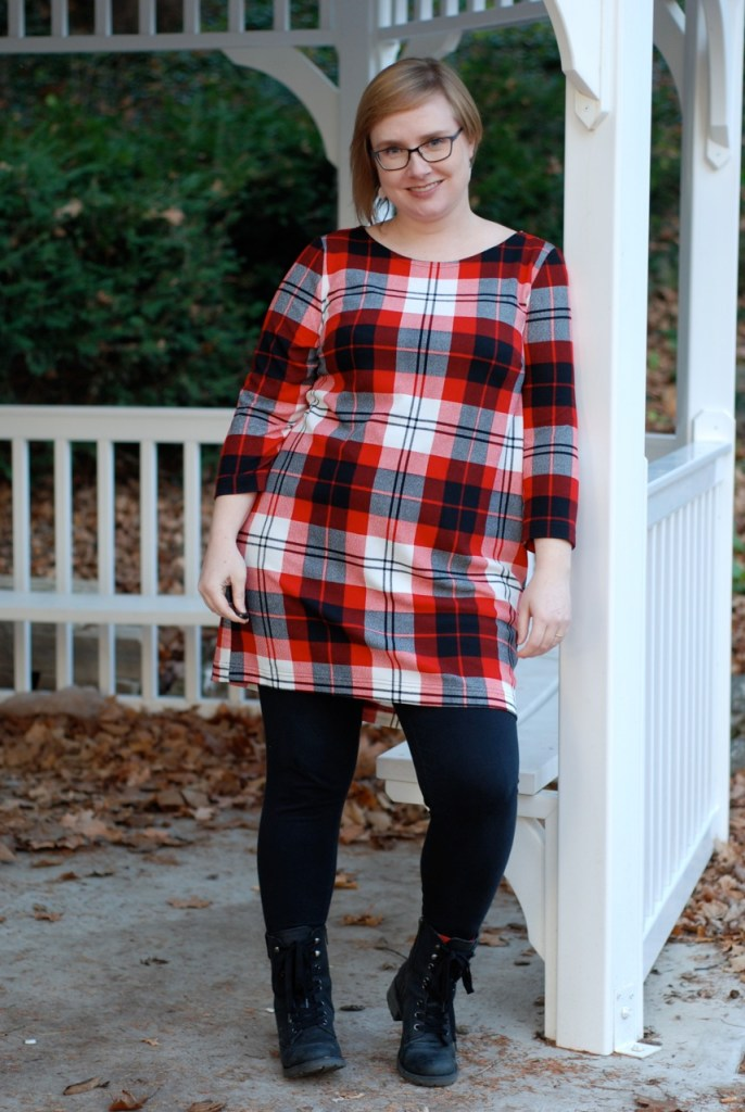 In an older photo, Gillian wears a fitted red-white-and-black plaid dress over leggings and boots.