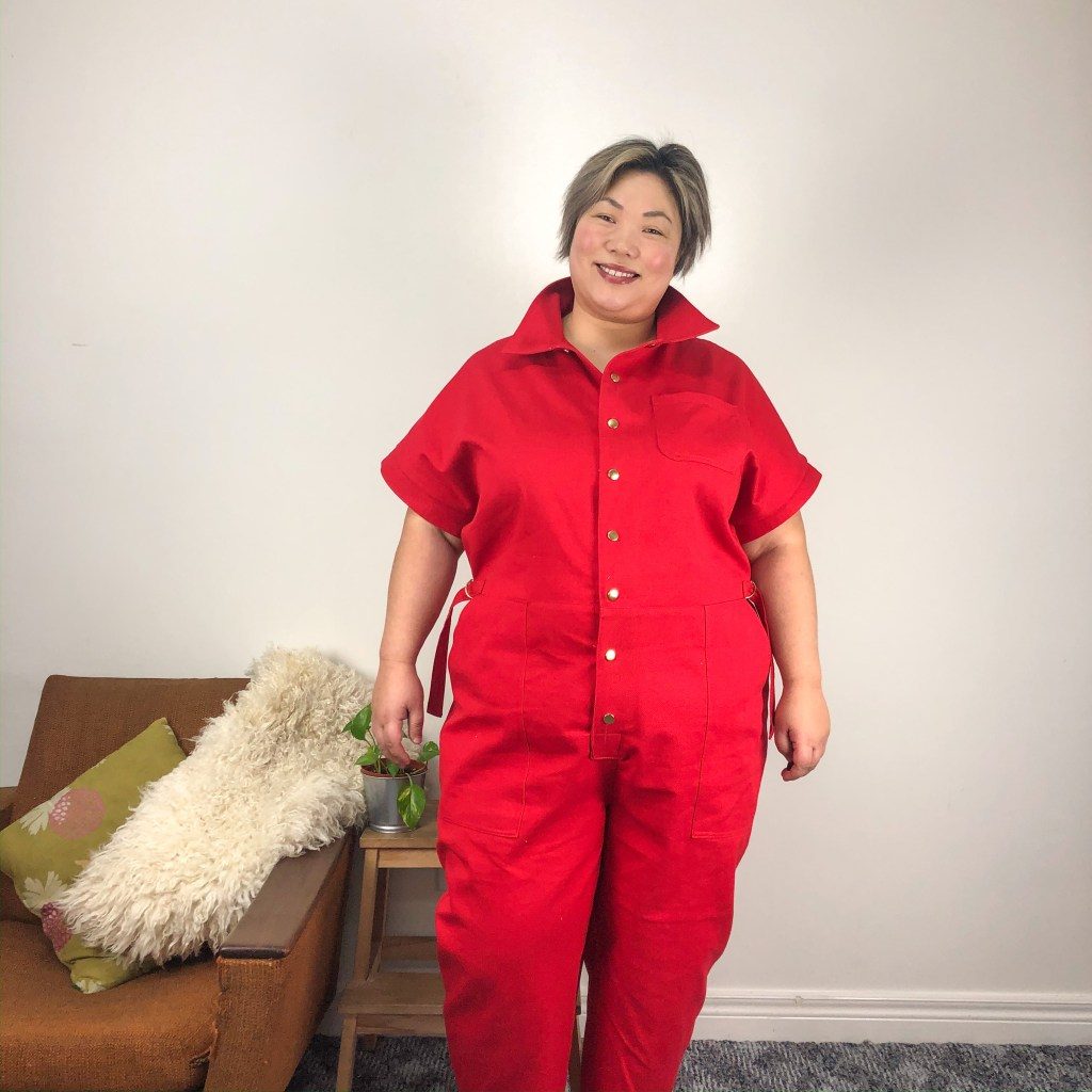 Leila wears a bright red boilersuit with short sleeves, waist ties, and brass fastenings.