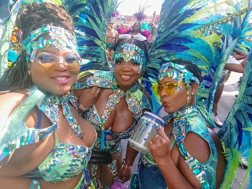 Martha and two friends pose for a selfie win their matching Carnival costumes. It's possible to see the glitter, metallic vinyl, and beadwork on their costumes!