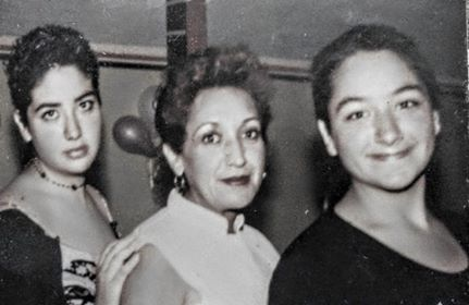 Black and white photo of three women, the center one older than the other two