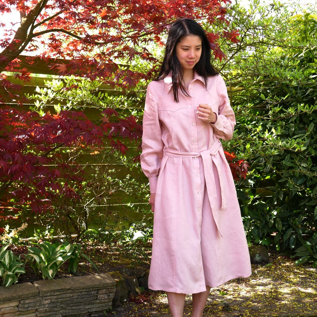 Kate wears a pale pink linen shirt-dress with a waist tie. She stands in front of a lush garden of ornamental trees.