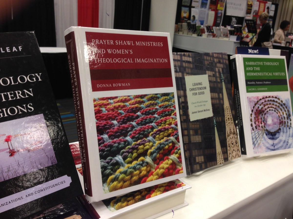 """A book titled """"Prayer Shawl Ministries and Women's Theological Imagination"""" by Donna Bowman is propped up next several other academic books. The cover of the book has a photo of a colorful basketweave knitting pattern."""