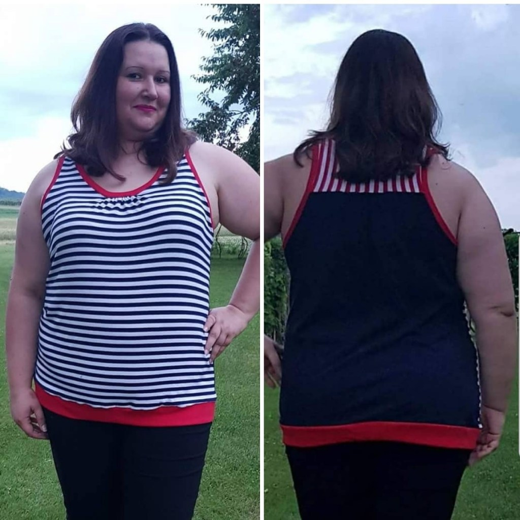 Person modeling a black and white striped tank top with red accents