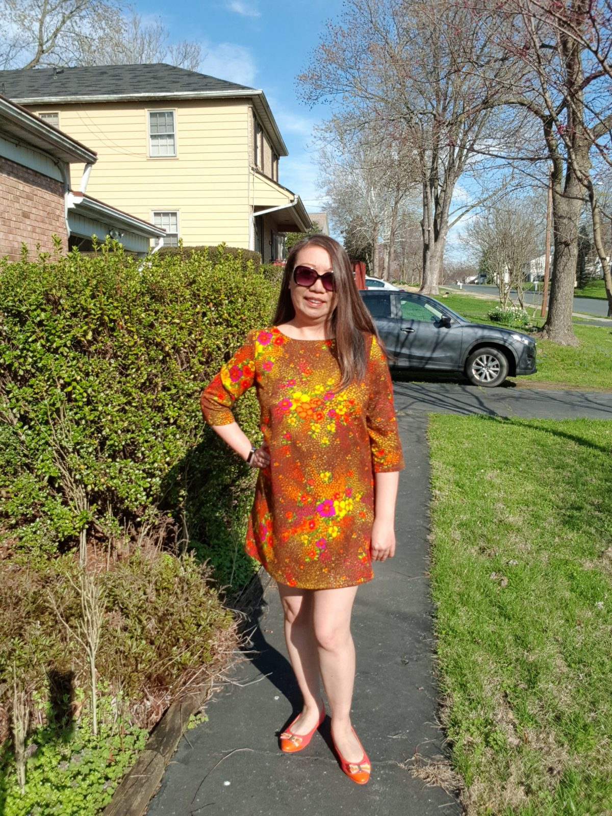 Margy is standing on a sidewalk in a neighborhood. She is wearing a red, orange, and yellow shift-style dress that has three-quarter length sleeves. She is also wearing sunglasses and orange flats that have bows on them.