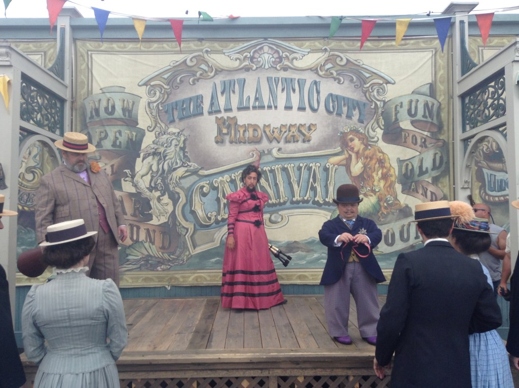 An image from the TV show Boardwalk Empire, showing a carnival scene with several people on stage and others watching, all wearing period clothing.