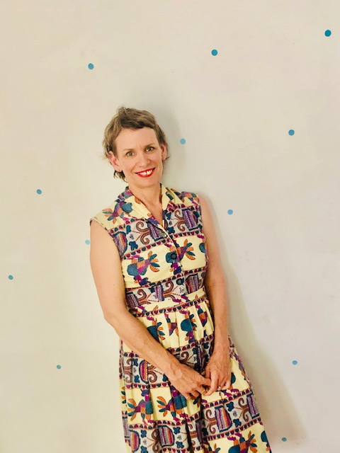Joanne stands in front of a light colored wall that has small blue polka dots. She has short, light brown hair and is wearing red lipstick and a sleeveless button-front dress. The dress' fabric has a banded abstract design with purple, blue, mustard, and cream colors.