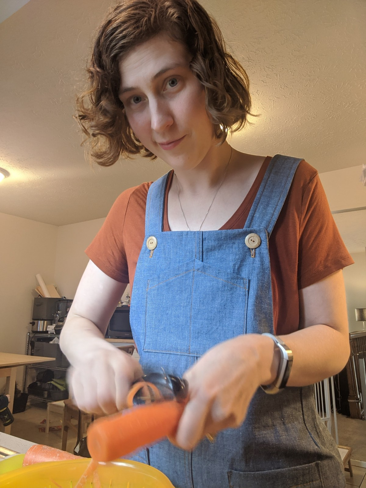 A white woman with short, curly brown hair looks down at the camera. She is wearing a brown short-sleeved t-shirt and light colored denim overalls. She is peeling a carrot.
