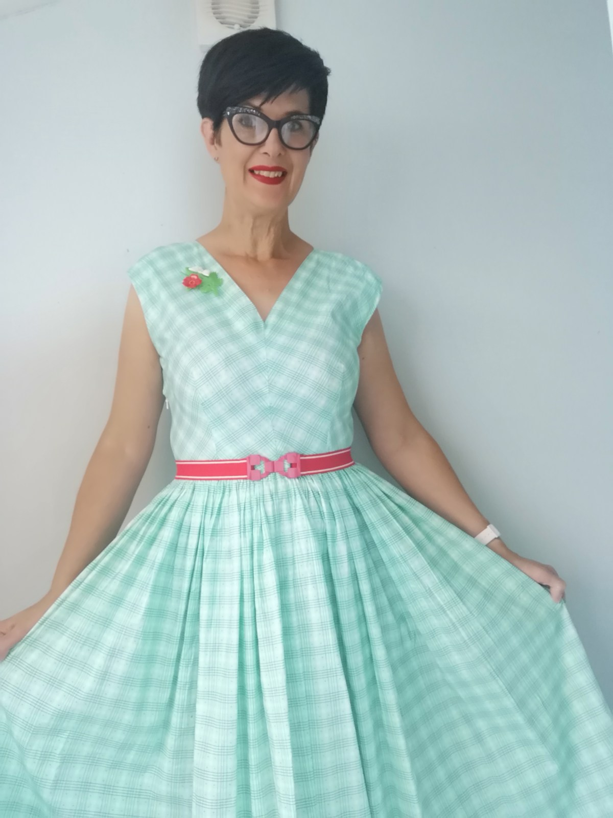 A white woman with short dark hair, 1960s-style glasses, and red lipstick holds the sides of the skirt on her dress. The dress is light blue and white gingham with a v neckline and has a pink belt.