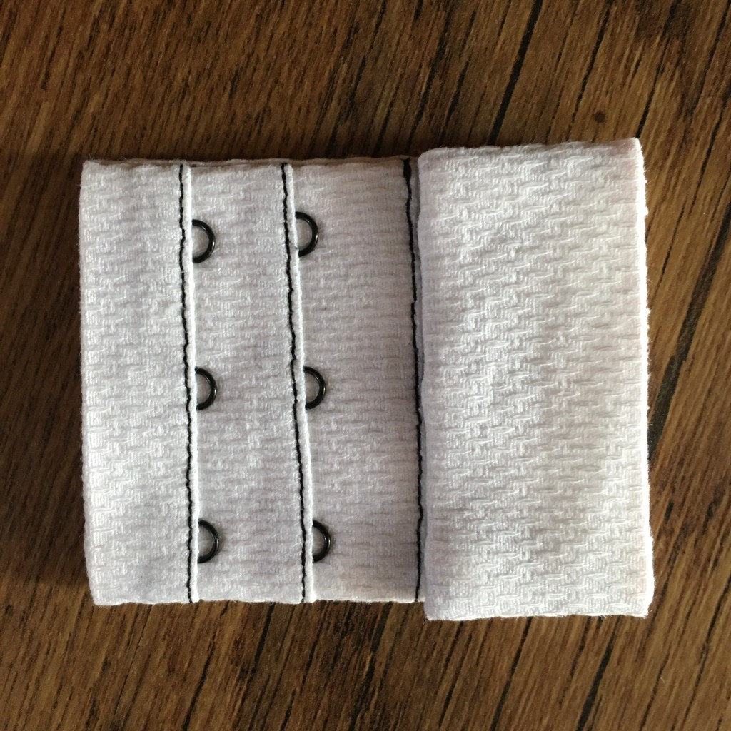Completed hook and eye closure that is white with black hooks and eyes and stitching