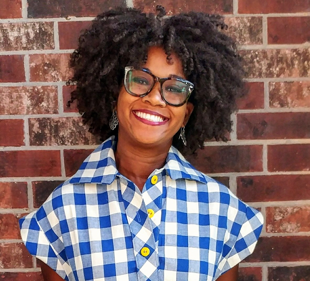 A smiling Black woman with glasses, red lipstick, and silver earrings. She has on a collared top or dress bodice that is blue and white gingham with yellow buttons.