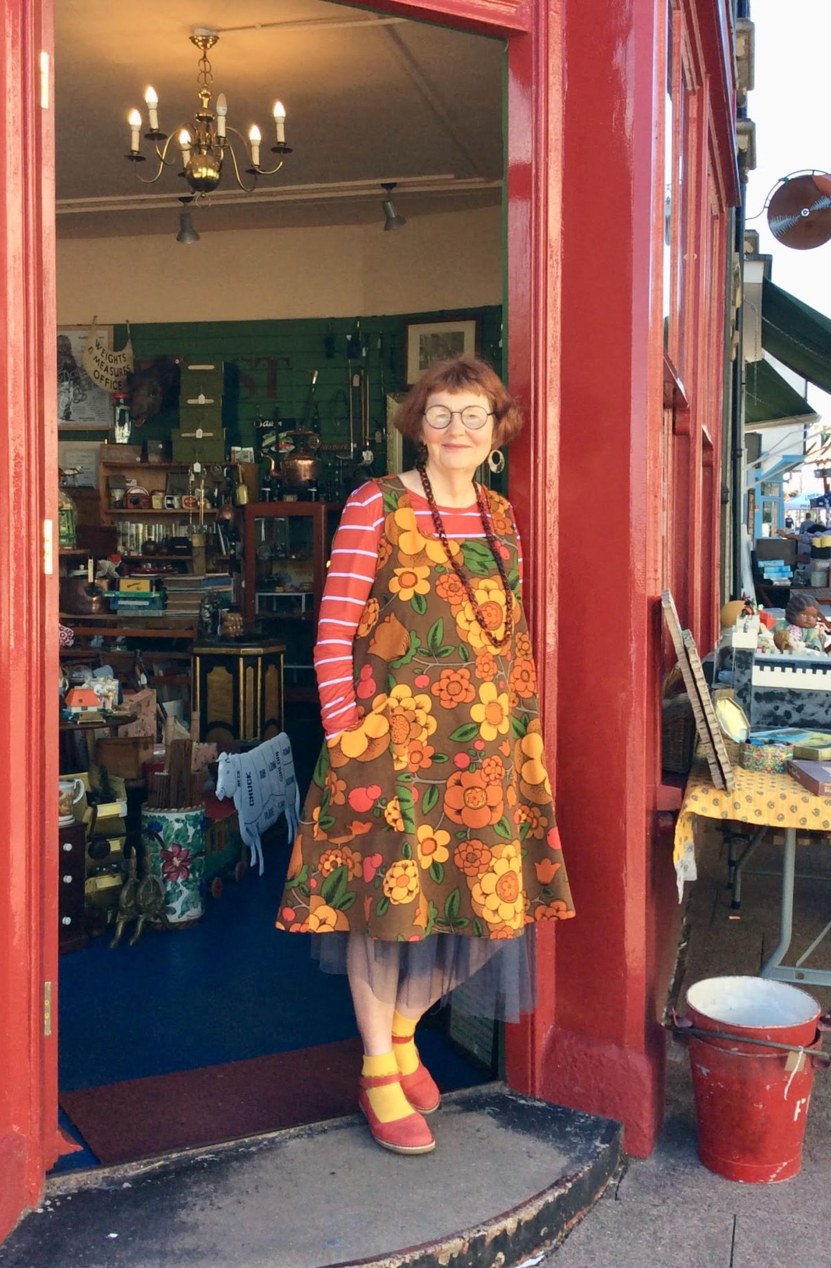 Marcia stands in the doorway to an antique shop. She has short brownish-red hair and wears glasses. She is wearing an A-line pinafore dress with a 1970s design. The colors on her dress are brown, yellow, green, orange, and red. She is wearing a red and white striped shirt and a long necklace as well. On her feet are yellow socks and red mary jane shoes.