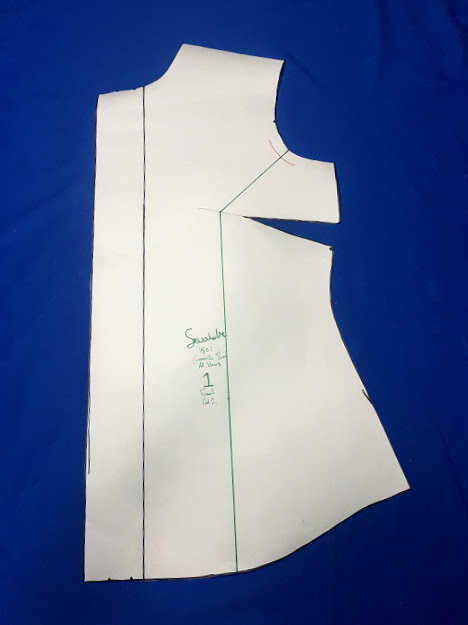 Shirt pattern piece that shows green marker line drawn as described above: through the armscye and pivoting at the chest point, vertical to the bottom of the pattern piece.