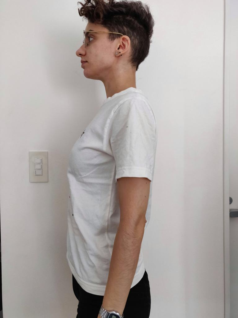 Emilia stands in profile in the same white tee shirt, this time with the merino tank underneath. There is little bust definition, but there is also very little compression.