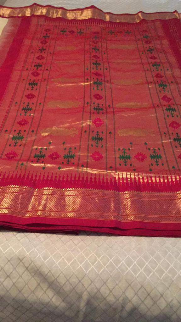 The wide border (pallau) of the off-white Paithani. It has geometric diamond motifs in red and green.
