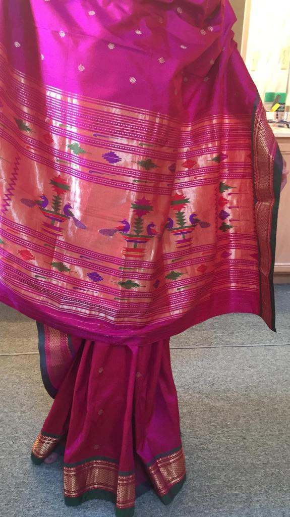 A traditional Paithani draped so that we see most of the design. The colour is fuschia pink, with gold edging. It has a wide border  (pallau) at one end with a recurring motif of 2 peacocks at a fountain, woven in purple, red and green.