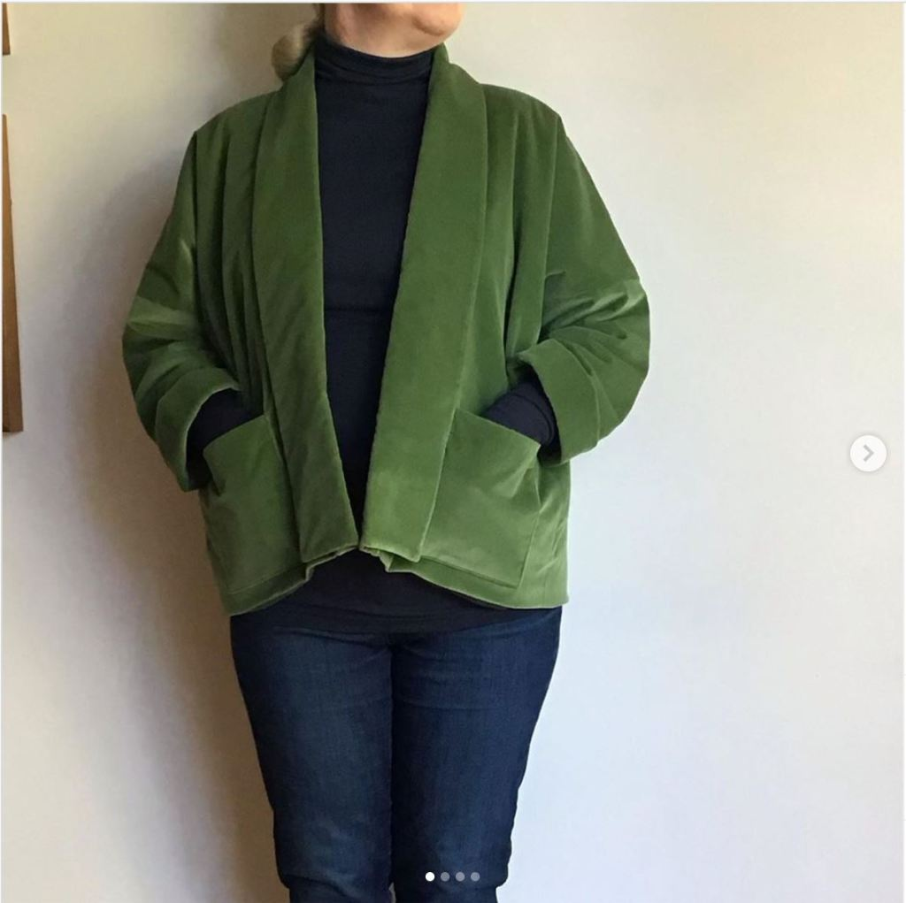 A picture of a person wearing jeans and a soft green velvet cord jacket.  The head is cut off and they are leaning against a cream wall with their hands in the jacket pockets.
