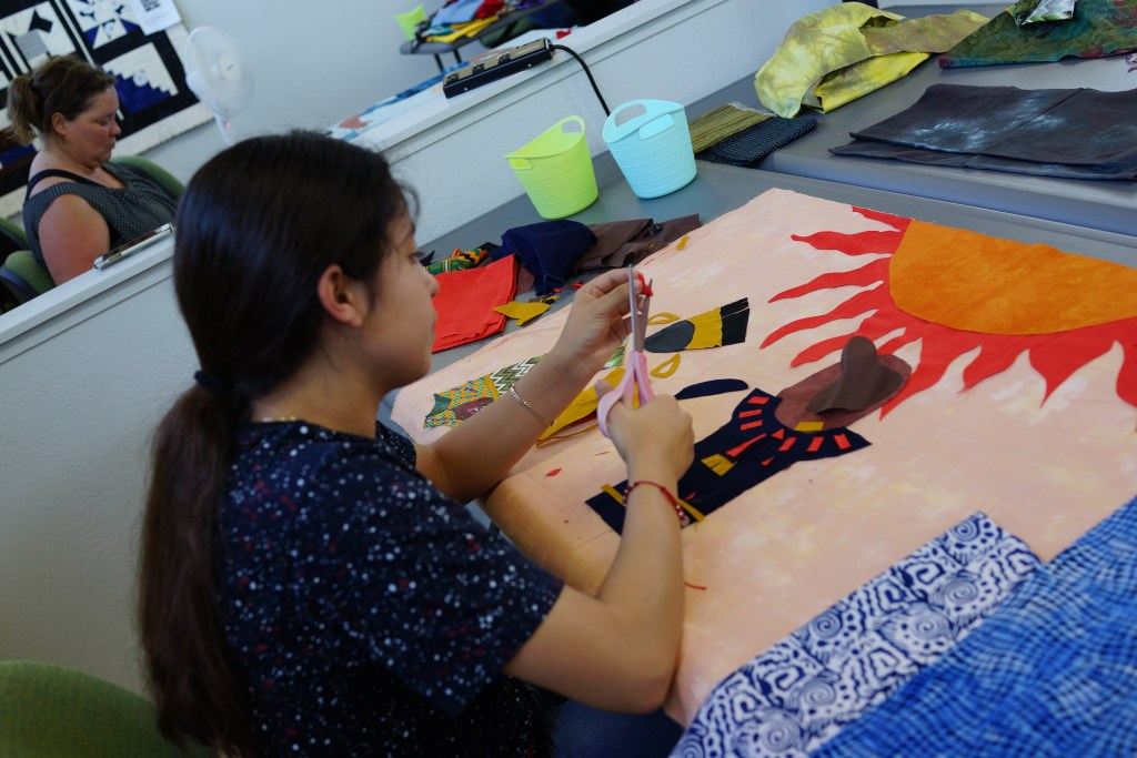 A young person cuts fabric and lays out fabric pieces to create a picture of a person standing below the sun.