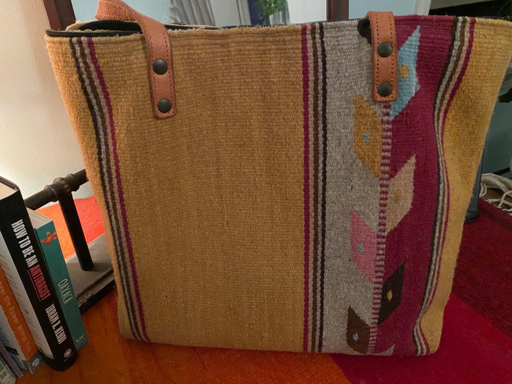 A tote bag with leather handles stand on a dresser. It is made from a woven tapete textile, in stripes of yellow and pink, with a vertical diamond motif.