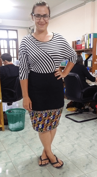 Image of a woman with hair in a bun and wearing glasses wearing a striped black and white 3/4 sleeve top and a skirt with a black section and a colorful, geometric border, and black flip flops