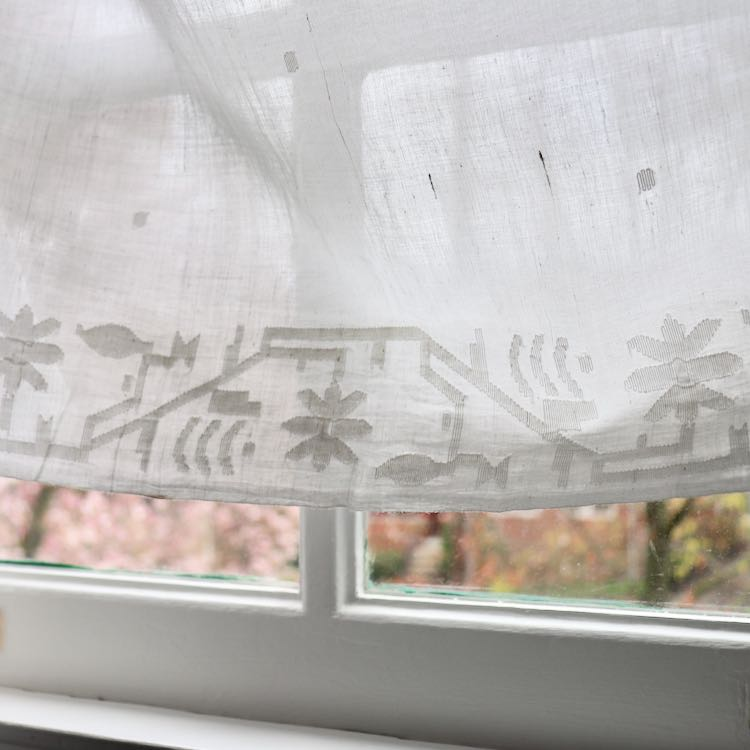 Jamdani cotton fabric with white on white floral border design, shown in front of window