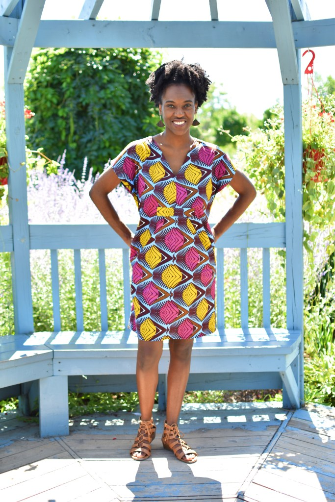 Person in a knee-length dress made of Ankara print with yellow, pink and other colors.