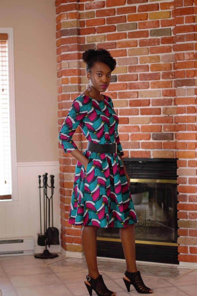 Full-length photo of a person in a below the knee length dress made of Ankara fabric in teal, dark pink and other colors