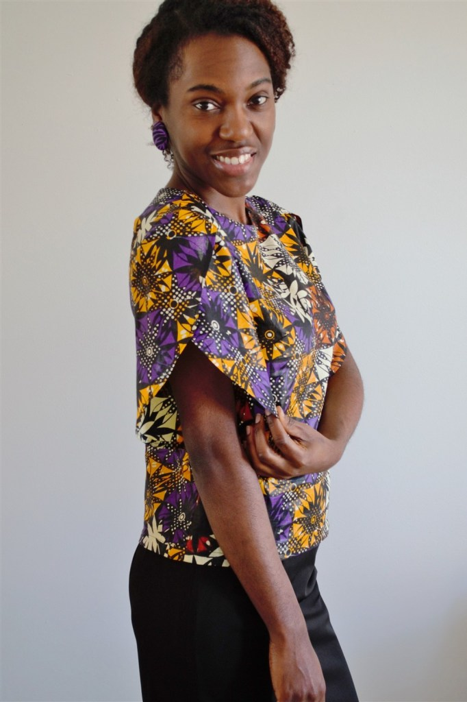 Person in a short-sleeved top made of an Ankara print with purple, yellow and other colors
