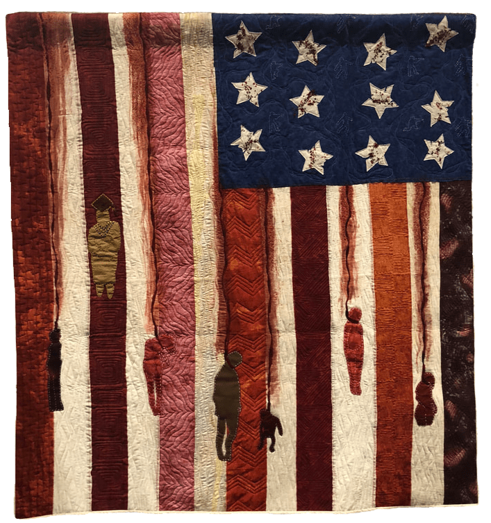 A quilt that resembles the American flag on its side but has people being hanged on it and streaks resembling blood.