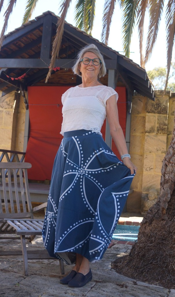 Sue stands in a garden wearing the zero waste Clair Skirt, made from a thrifted duvet cover which has a large -scale blue and white print. She is also wearing a cropped white t-shirt.