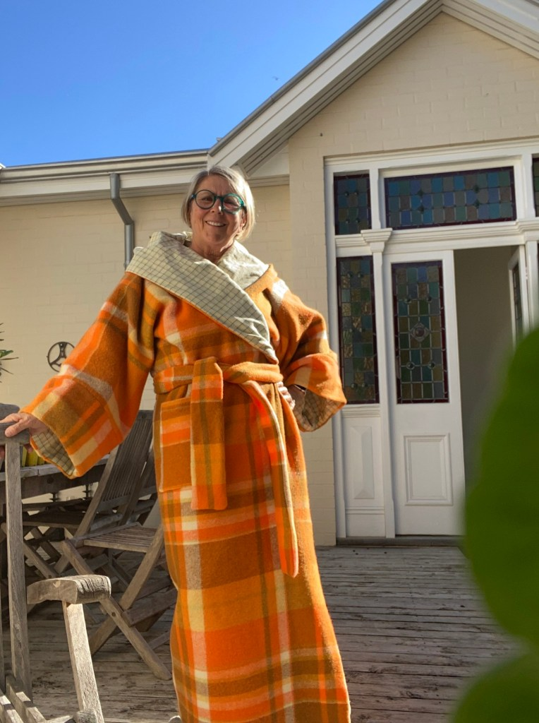 "Sue stands in front of a door and garden furniture, wearing a bathrobe from Liz Haywood's book ""Zero Waste Sewing"". The bathrobe is made from an ornage plaid vintage blanket and duvet cover."