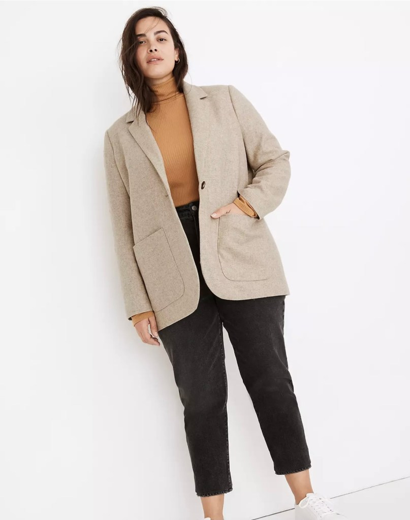 A young woman against a white wall wears cropped, straight leg black jeans with a pumpkin-coloured long sleeve turtleneck tucked into the waist band. She is wearing a boxy, loose blazer in a neutral oatmeal colour; the blazer has narrow lapels down to a single button just under bust level, and a single huge pocket on each side of the front. The pockets go from waist to a couple of inches above the hem, and are almost as wide as each front piece. White sneakers complete her relaxed pose.