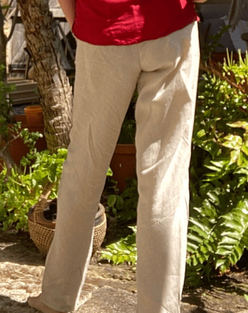 A person stands in a garden, wearing the spiral trousers, made up and sewn in natural colour linen.
