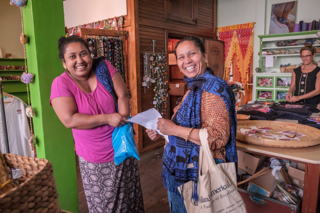 Two women stand beside each other looking at the camera with big smiles on their faces. One is holding a bag of items, and the other a piece of paper. They are standing in the Stitch Buffalo store and are surrounded by handmade goods.