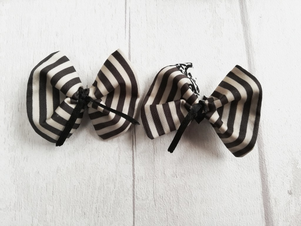 Two hair bow clips in the same black and white stripy fabric as the trousers. The bows fan out wide at the edge and are cinched in, in the centre with a thin black ribbon.