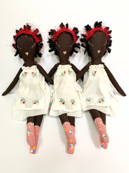 Three rag dolls sit together. They have brown fabric bodies, black wool hair, white embroidered dresses and red check feet.