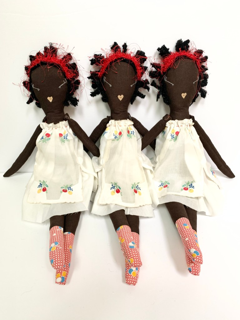 Three rag dolls as per the previous image sit together.