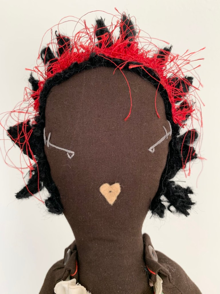 A close-up of one of the brown cloth dolls, showing embroidered facial features, black wool hair and red headscarf.