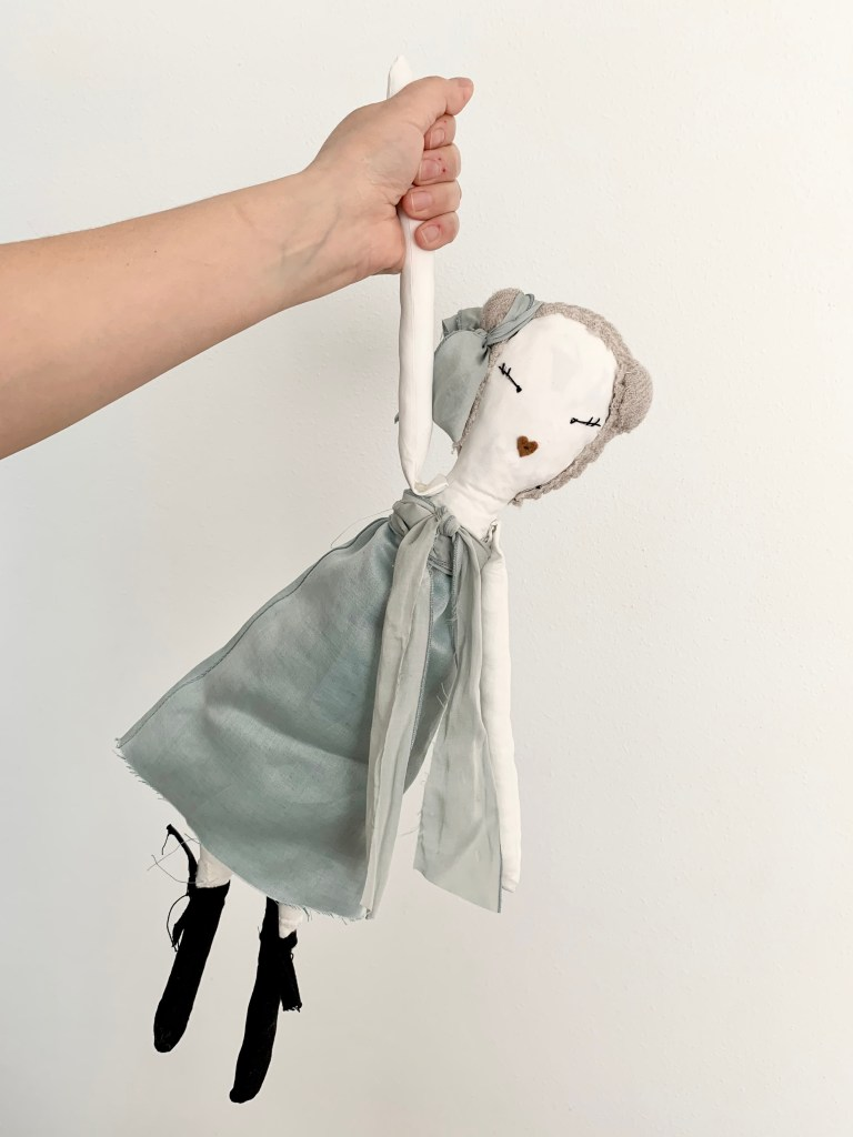 A hand holds a rag doll by it's arm. The doll has a white cloth body, grey hair, and is dressed in a pale blue dress.