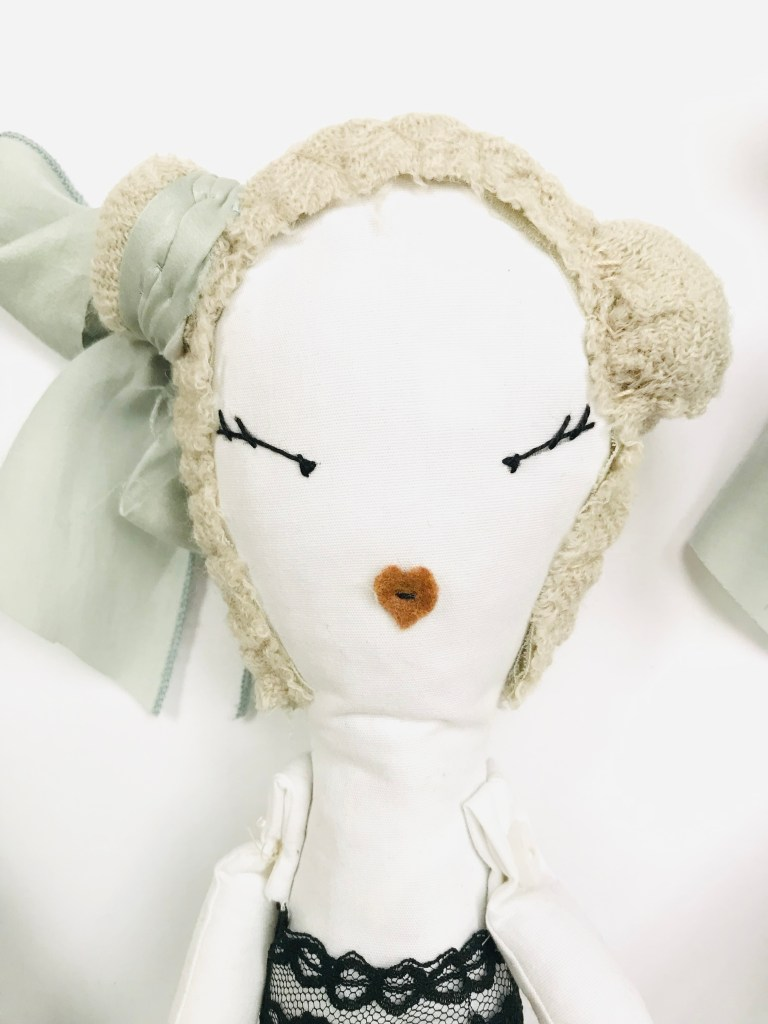 A close-up of the first doll, showing embroidered eyes,  small felt mouth and blue silk headscarf.