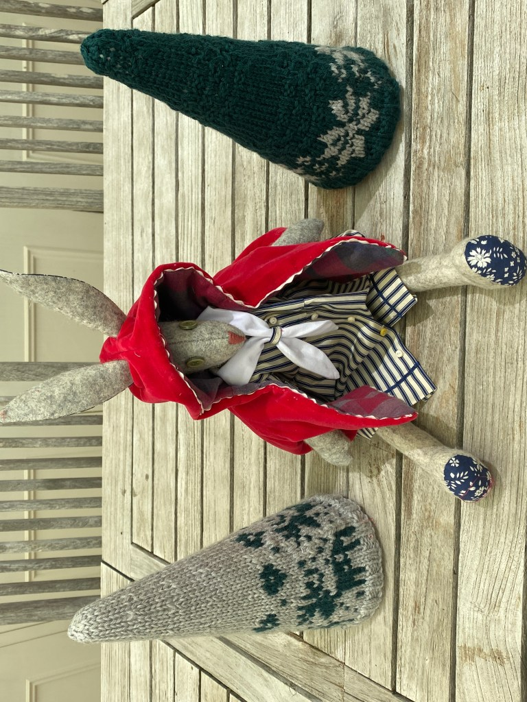 A Luna Lapin toy rabbit dressed in a sailor dress and red silk velvet cape. The toy sits on a wooden table and is flanked by two knitted cones with reindeer and snowflake fair isle patterns.