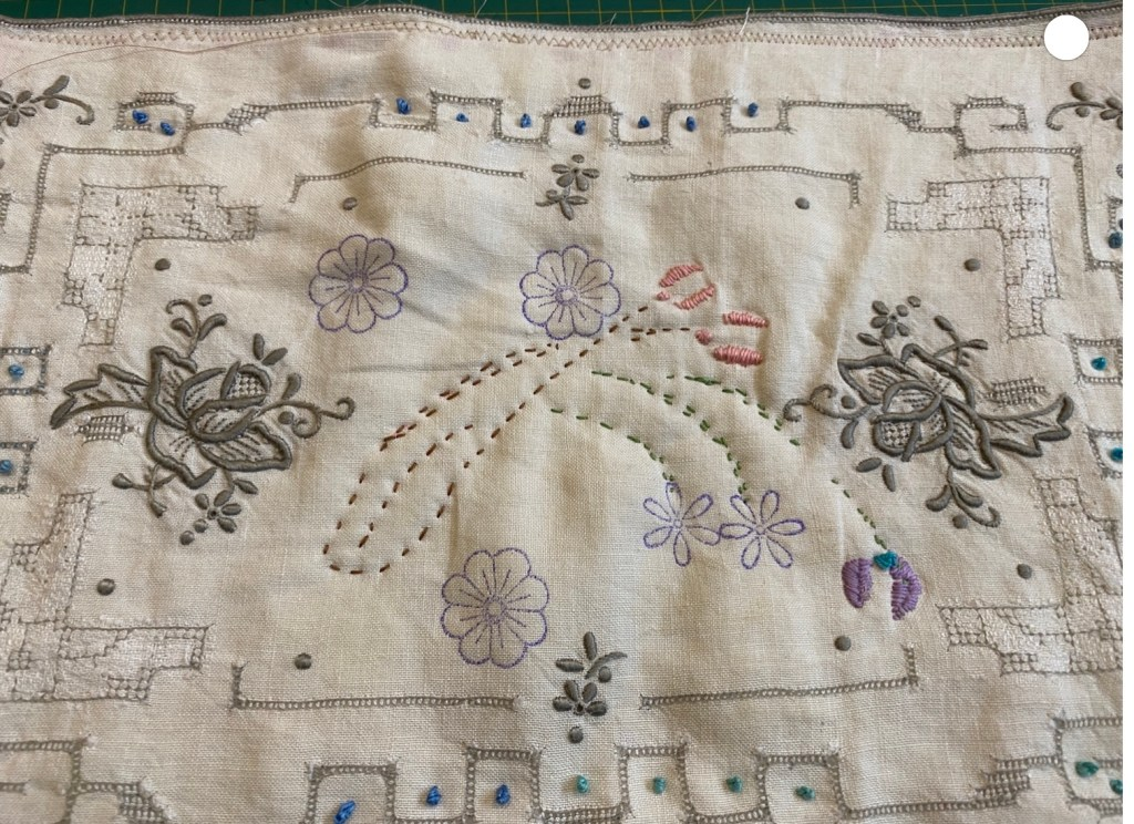 A piece of machine embroidered linen, formerly a table mat, which has been further embroidered by hand.