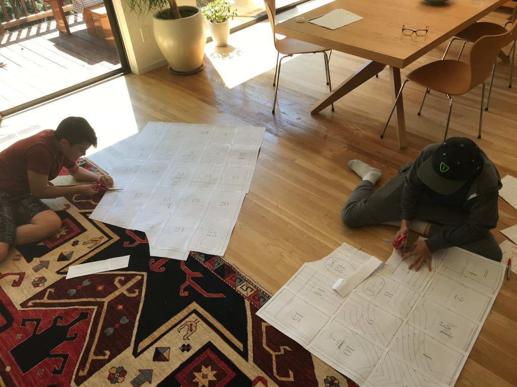 Two teenagers cutting out PDF patterns on the floor
