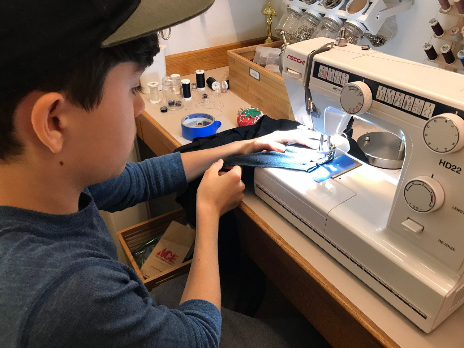 A side view of a teenager sitting at a sewing machine
