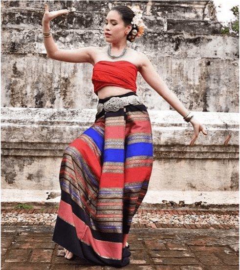 A Thai woman wearing a traditional and brightly colored sarong and wrapped sleeveless top.  She is in a dance pose with flowers in her dark hair.