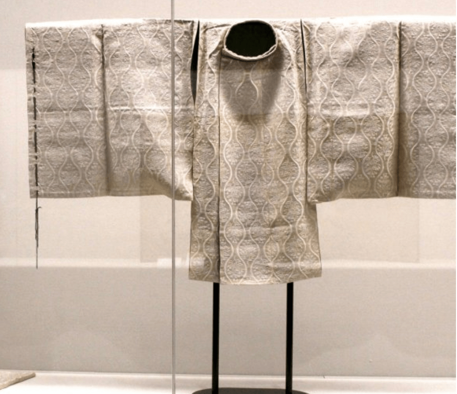 An example of a traditional, historical Japanese garment. the garment is white silk with a wave pattern throughout. The garment is displayed on a stand as if in a museum.
