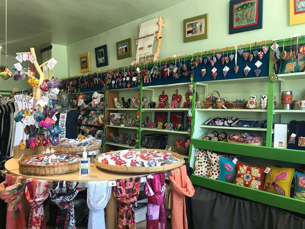 The interior of the Stitch Buffalo boutique that has light green painted walls lined with colourful handmade crafts including hanging ornaments, small household items, and pillows. At the front of the photo, to the left hand side is a table that includes scarves, brooches and more colourful ornaments.