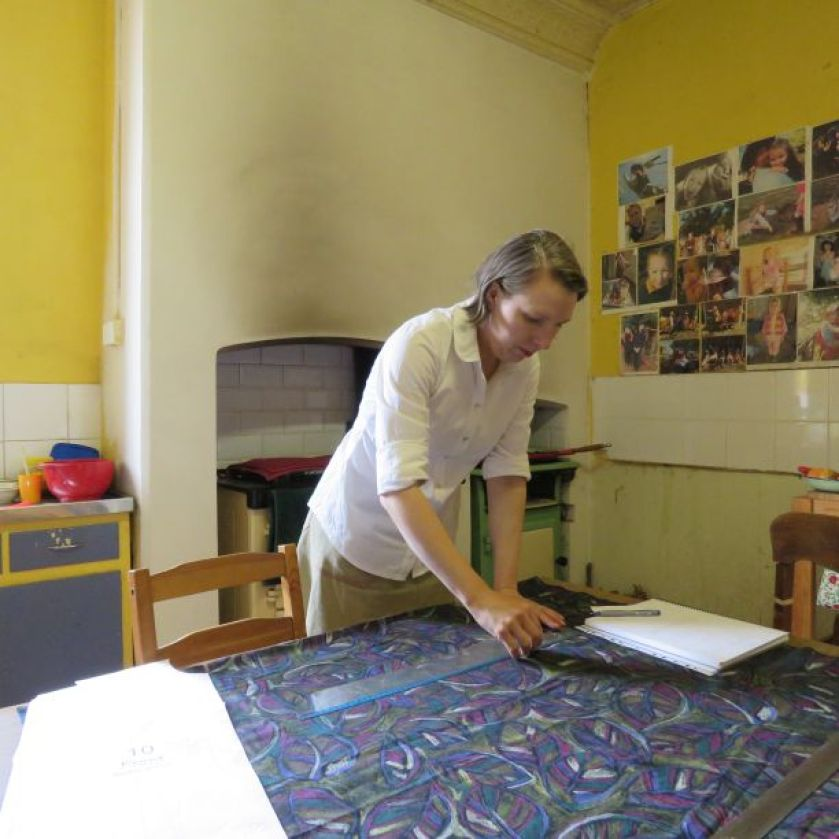 Image of a woman in a kitchen marking a pattern onto the fabric