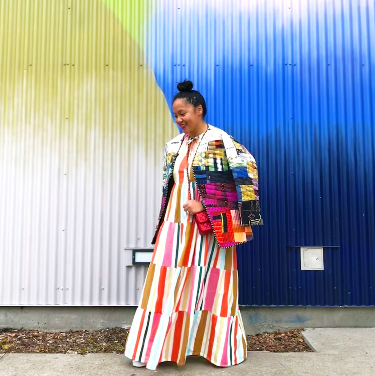 A person standing in front of a yellow and blue wall wearing a colourful quilted jacket made out of scraps with a long striped dress underneath.