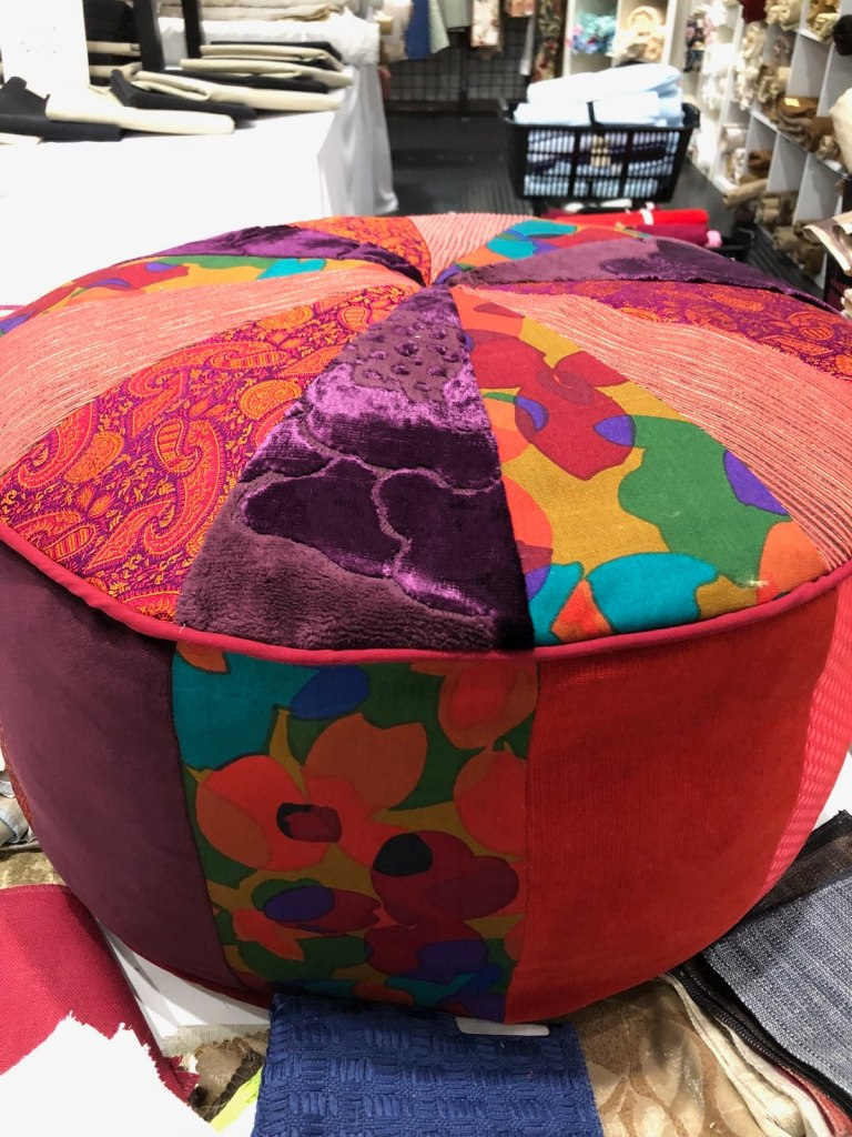Closet Core Pattern Pouf filled with scraps. The circular pouf is mostly red and is split into 12 sewn pieces with 4 alternating patterned fabrics.