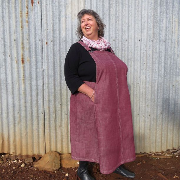 A model wearing a pink Smith Pinafore dress, standing in front of a background of grey corrugated iron.
